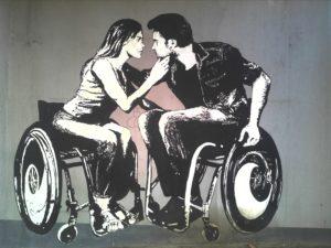 Na sliki sta narisana moški in ženska na invalidskem vozičku, ki sta zaljubljena.