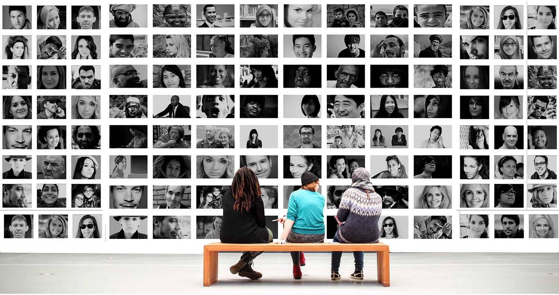 Na fotografiji tri osebe sedijo na klopi v galeriji in gledajo množico fotografij, ki portretov