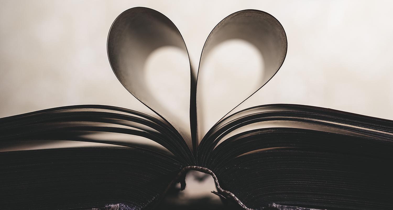 Na fotografiji je odprta knjiga z dvema upognjenima listoma v obliki srca.